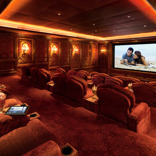Photo of a traditional enclosed home cinema in Los Angeles with red walls, carpet, a projector screen and red floors.