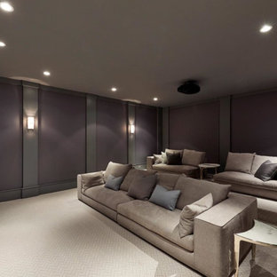 This is an example of a large transitional enclosed home theatre in New York with purple walls, carpet, a projector screen and beige floor.