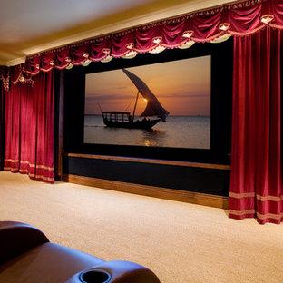 Exemple d'une grande salle de cinéma chic fermée avec un écran de projection, un mur rouge et moquette.
