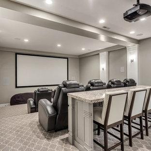 Immagine di un grande home theatre stile americano chiuso con pareti grigie, moquette, schermo di proiezione e pavimento grigio