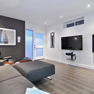 Foto di un home theatre contemporaneo aperto con pareti bianche, pavimento in laminato e TV a parete