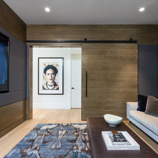 Inspiration for a contemporary enclosed home theatre in Vancouver with brown walls, light hardwood floors, a wall-mounted tv and beige floor.