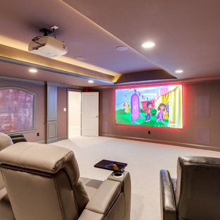 This is an example of a transitional enclosed home theatre in DC Metro with purple walls, dark hardwood floors, a projector screen and brown floor.
