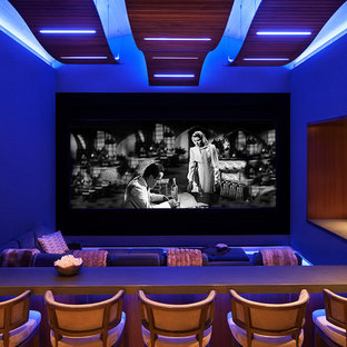 Example of a huge mountain style enclosed home theater design in Denver with a projector screen