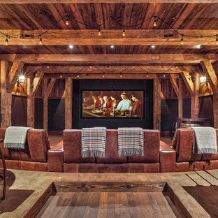 Inspiration for a huge rustic enclosed medium tone wood floor and brown floor home theater remodel in Other with brown walls and a projector screen