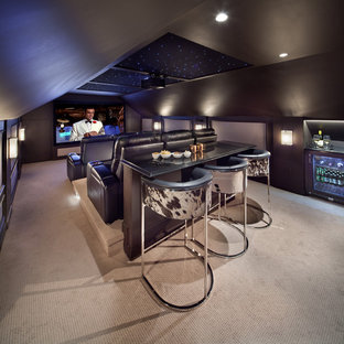 This is an example of a large contemporary enclosed home theatre in DC Metro with brown walls, carpet and a projector screen.