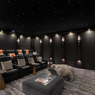 Trendy enclosed carpeted and gray floor home theater photo in Orange County with black walls