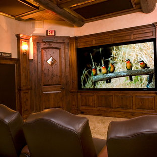 This is an example of a large country open concept home theatre in Seattle with beige walls, slate floors and a projector screen.