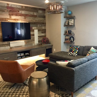 Photo of a mid-sized transitional home theatre in Denver with laminate floors, a wall-mounted tv and brown floor.