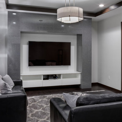 Mid-sized trendy open concept dark wood floor and brown floor home theater photo in Orlando with gray walls and a wall-mounted tv