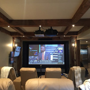 Inspiration for a large rustic open concept carpeted and beige floor home theater remodel in Other with a projector screen and gray walls