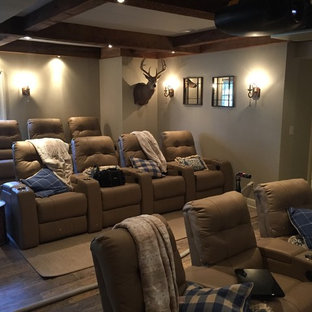 Example of a large mountain style open concept medium tone wood floor and brown floor home theater design in Other with gray walls and a projector screen