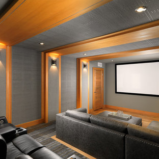 This is an example of a mid-sized modern enclosed home theatre in Vancouver with grey walls, medium hardwood floors and a projector screen.