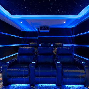 Ispirazione per un piccolo home theatre moderno chiuso con pareti nere, moquette, schermo di proiezione e pavimento blu