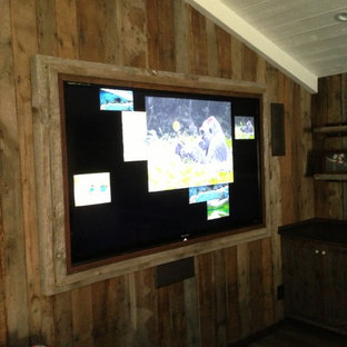 Design ideas for a mid-sized country enclosed home theatre in Los Angeles with brown walls, dark hardwood floors and a built-in media wall.
