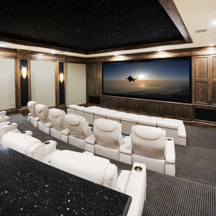 Example of a huge classic enclosed carpeted and multicolored floor home theater design in Austin with beige walls and a projector screen