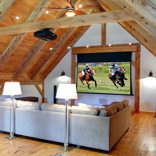 Diseño de cine en casa tradicional con paredes blancas, suelo de madera en tonos medios y pantalla de proyección