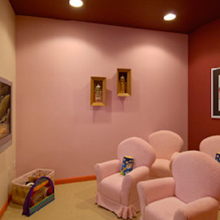 This is an example of an enclosed home theatre in DC Metro with pink walls, carpet and a wall-mounted tv.