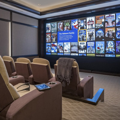 Home theater - large traditional enclosed carpeted and multicolored floor home theater idea in Miami with beige walls and a projector screen