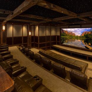 Cette image montre une très grande salle de cinéma traditionnelle fermée avec un mur beige, moquette, un écran de projection et un sol beige.