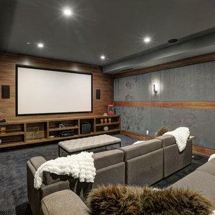 Abgetrenntes, Großes Modernes Heimkino mit grauer Wandfarbe, Teppichboden, Wand-TV und schwarzem Boden in Los Angeles