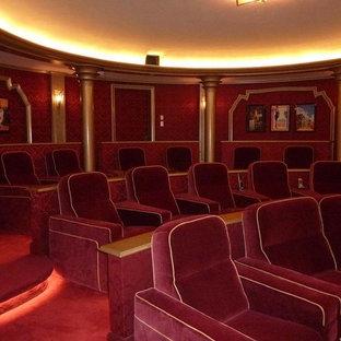 Cette photo montre une très grand salle de cinéma éclectique fermée avec un mur rouge, moquette, un écran de projection et un sol rouge.