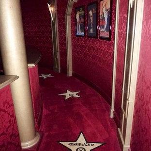 Exemple d'une très grand salle de cinéma éclectique fermée avec un mur rouge, moquette, un écran de projection et un sol rouge.