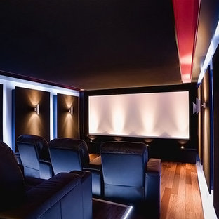 Photo of a mid-sized modern enclosed home theatre in Minneapolis with light hardwood floors, a projector screen and black walls.