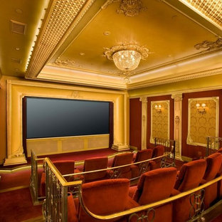 Home theater - traditional enclosed carpeted and red floor home theater idea in Los Angeles with a media wall