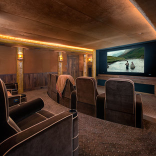 Example of a mountain style carpeted and brown floor home theater design in Other with brown walls and a projector screen