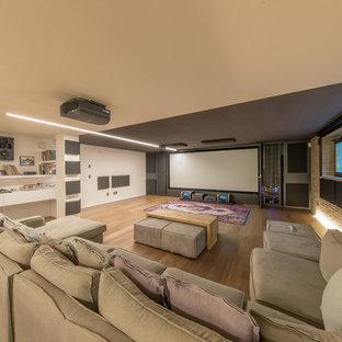 Esempio di un grande home theatre design con pareti bianche, schermo di proiezione, parquet chiaro e pavimento beige