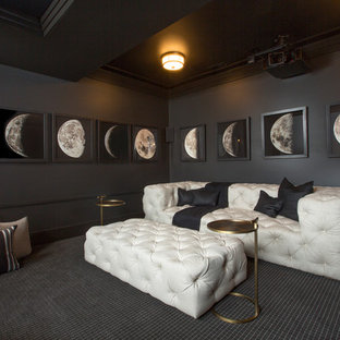 Diseño de cine en casa actual con paredes negras, pantalla de proyección y suelo negro