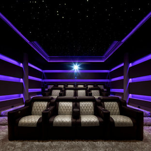 This is an example of a mid-sized modern enclosed home theatre in New York with purple walls, carpet, beige floor and a built-in media wall.