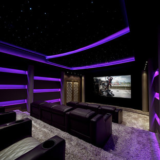 Photo of a large contemporary enclosed home cinema in New York with black walls, carpet, a built-in media unit and beige floors.