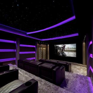 Cette photo montre une grand salle de cinéma tendance fermée avec un mur noir, moquette, un téléviseur encastré et un sol beige.