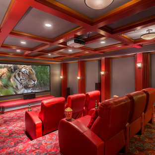 Photo of a classic enclosed home cinema in Seattle with grey walls, carpet, a projector screen and red floors.