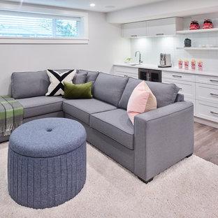 Kleines, Offenes Klassisches Heimkino mit weißer Wandfarbe, Laminat, Wand-TV und braunem Boden in Vancouver