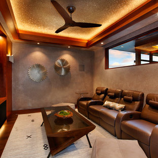 Immagine di un home theatre tropicale chiuso con parete attrezzata, pareti marroni e parquet scuro