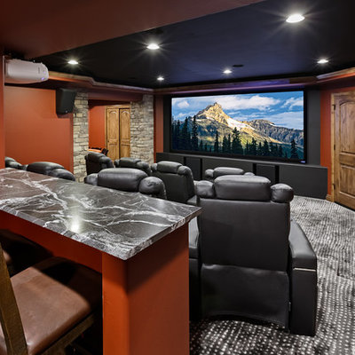 Home theater - large traditional enclosed carpeted and gray floor home theater idea in Denver with orange walls and a projector screen