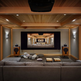 Example of a mountain style enclosed carpeted and gray floor home theater design in Seattle with gray walls and a projector screen