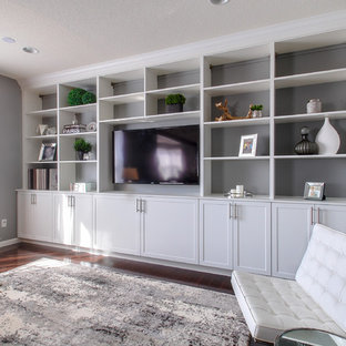 This is an example of a large contemporary open concept home theatre in Minneapolis with grey walls, dark hardwood floors and a built-in media wall.