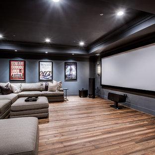 Esempio di un grande home theatre stile americano aperto con pareti blu, pavimento in legno massello medio e schermo di proiezione