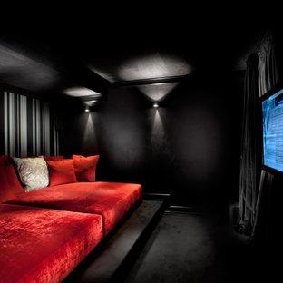 Immagine di un home theatre design con pareti nere, moquette, TV a parete e pavimento nero