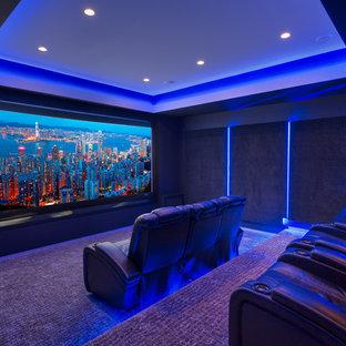 Idee per un grande home theatre moderno chiuso con pareti nere, moquette, schermo di proiezione e pavimento viola