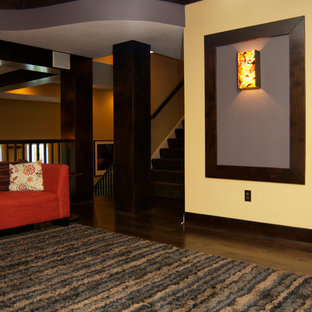 Inspiration for a large modern enclosed home theatre in Kansas City with purple walls, dark hardwood floors, a wall-mounted tv and brown floor.