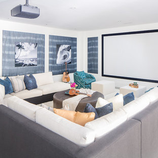 Home theater - beach style concrete floor and gray floor home theater idea in Orange County with white walls and a projector screen