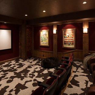 Example of a large mountain style enclosed carpeted and multicolored floor home theater design in Other with red walls and a projector screen