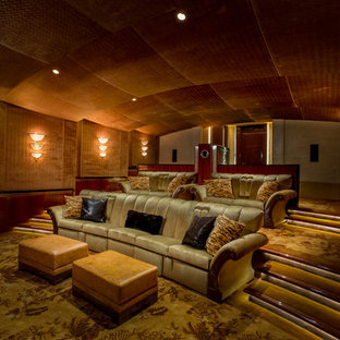 Photo of a mediterranean enclosed home theatre in San Francisco with orange walls, carpet, a projector screen and multi-coloured floor.