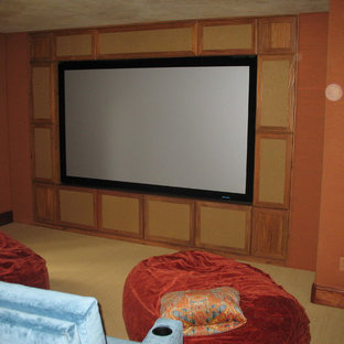 Inspiration for a mid-sized traditional open concept home theatre in Denver with a built-in media wall, orange walls and carpet.