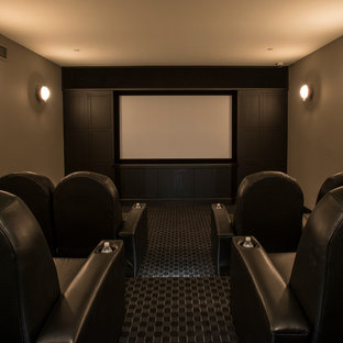 This is an example of a mid-sized modern enclosed home theatre in DC Metro with grey walls, carpet and a wall-mounted tv.